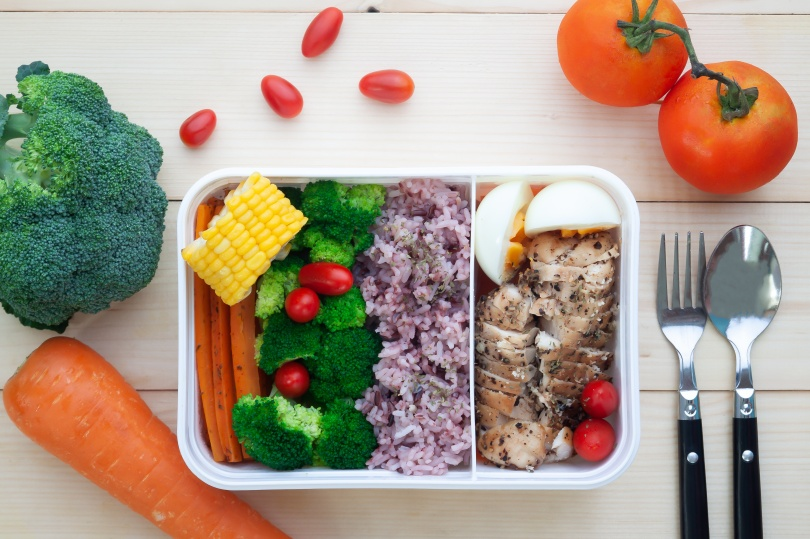 Directly above of healthy lunch box with vegetables, rice, boiled egg and chicken breast, Close up on wooden background